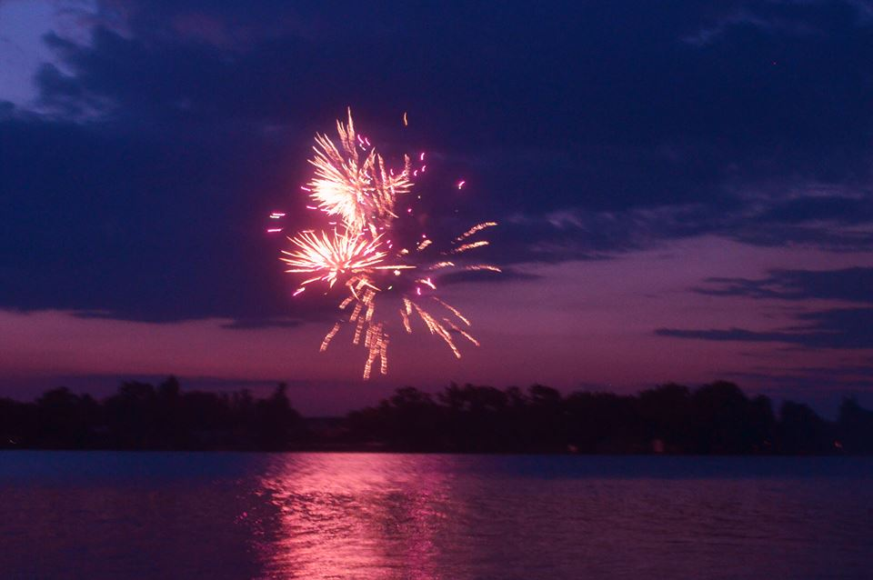 fireworks in night sky reflected on water